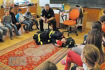 Patrik Mana (na zemi) a Jiří Čech (nad ním) názorně dětem ukazují, jak se mají zachovat v případě, když je ze spaní probudí hustý kouř.