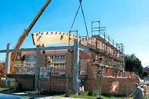 Nová tělocvična na Janáčkově náměstí v Krnově začíná získávat svou konečnou podobu. V těchto dnech dochází s pomocí jeřábu k osazování částí dřevěné konstrukce střechy.