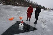 Instruktoři potápěčských činností kpt. Roman Kudela (žlutá přilba) a mjr. Martin Kučera (červená přilba) vedou nácvik ponoru pod ledem ve Svobodných Heřmanicích v zaplaveném lomu Šifr.