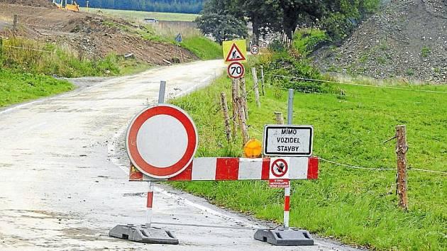 Uzavřená silnice z Karlovic do Holčovic. Vzniká zde vysoká hráz suchého poldru.