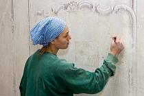 Restaurátorka Magda Bodanská skalpelem odstraňuje pozdější nátěry z nástěnných maleb v jídelně.