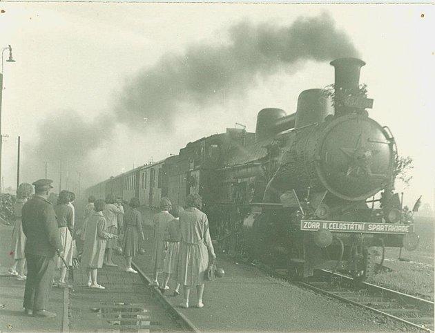 Nástupiště úvalenského nádraží vroce 1960.Železničáři museli mít na lokomotivě pěticípou hvězdu. Na náraznících jsou praporky a přání zdaru Spartakiádě. Dámy cestující smíči jsou pravděpodobně cvičenky.