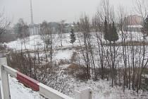 Vedle silnice za zábradlím začíná svah, který patří kraji. Dole pod svahem leží pozemky města.