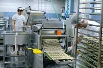Výroba tyčinek je poměrně jednoduchá, na začátku linky stroj těsto zamíchá, udělá z nich tenké proužky, naporcuje a pak jdou tyčinky do pece. Takhle to vypadá v nové pekárně v Bruntále.