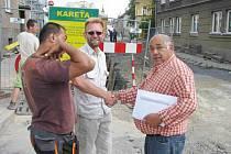 Roman Rubík, stavbyvedoucí firmy Kareta (uprostřed), podává po dokončení hrubých prací okolo teplovodu ruku majiteli stavební firmy Antonu Kokymu (vpravo).
