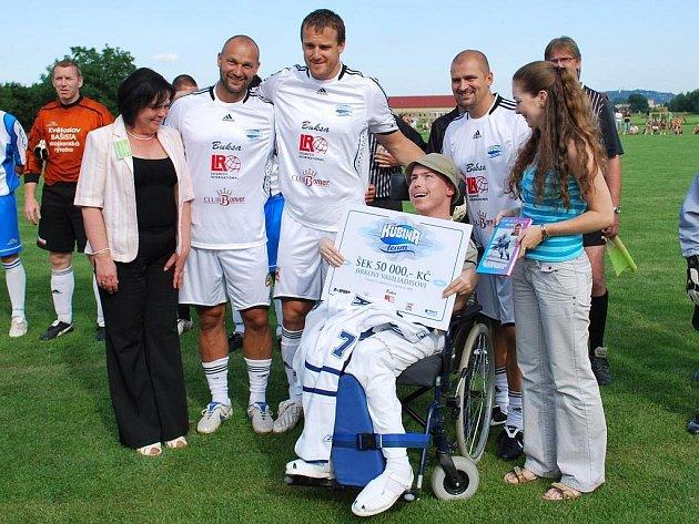 Pavel Kubina se svými spoluhráči předává šek na padesát tisíc korun postiženému Jiřímu Vasiliadisovi.