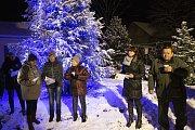 Lichnov zpíval koledy pod zasněženým a svítícím vánočním stromem.