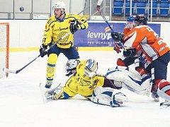 Krnovští hokejisté Ján Marienka a brankář Roman Šlupina se snaží čelit rožnovskému nájezdu.