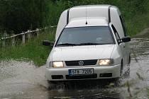 Řeka Opavice u Města Albrechtic se naplnila až po okraj, voda se dostala i na silnici.