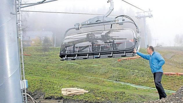 Skiareál Kopřivná dokončuje instalaci nové moderní šestisedačkové lanovky a nové červené sjezdovky. Spolumajitel areálu Karel Ležatka ukazuje, že sedačky lanovky budou kryté a vyhřívané.