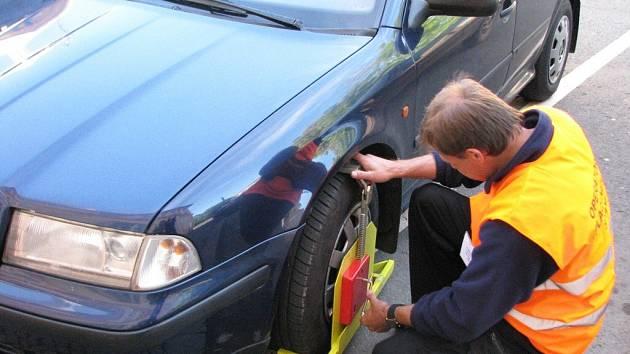 Pracovník technických služeb instaluje botičku na kolo majitele vozu, který nezaplatil za stání v centru Bruntálu.
