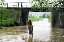 Podjezd v Krnově u Chářovského parku je už týden kvůli velké vodě uzavřený. Řidiči sice musí jezdit z Krnova do Brantic oklikou, ale chodcům stačí vyhrnout si nohavice.