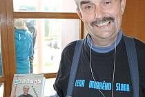 Rostislav Kuchař se svou knihou Uklízeč a ředitel. Oblečen je v bruntálském divadle do trička, které získal v celostátní soutěži O cenu modrého slona.