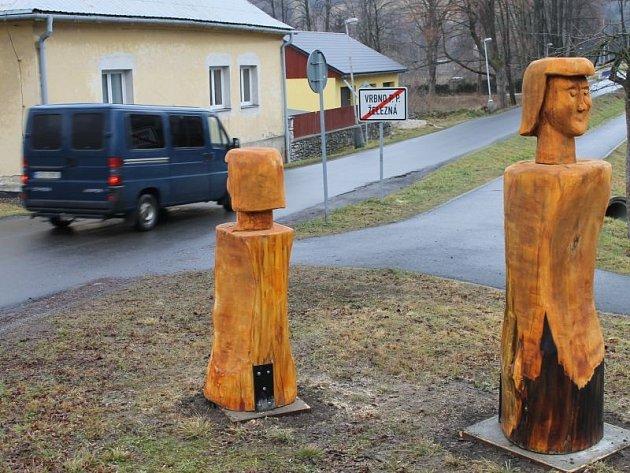 Dřevěné postavy vítají návštěvníky Železné, místní části Vrbna pod Pradědem. Dvě stojí na křižovatce, dvě u prodejny a jedna u zastávky.