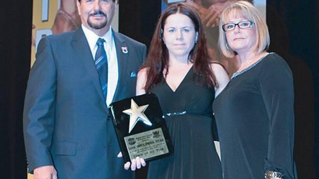 Eva Mistrová s oceněním, které získala za práci a rozvoj v oblasti fitness. Na snímku uprostřed mezi prezidentem INBA Dennym Kakosem a Dianou Kakos.