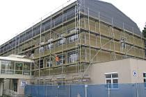 Dělníci na stavbě dokončují poslední úpravy na zateplení budovy, po kterém se začnou dodělávat další úpravy především v interiérech.
