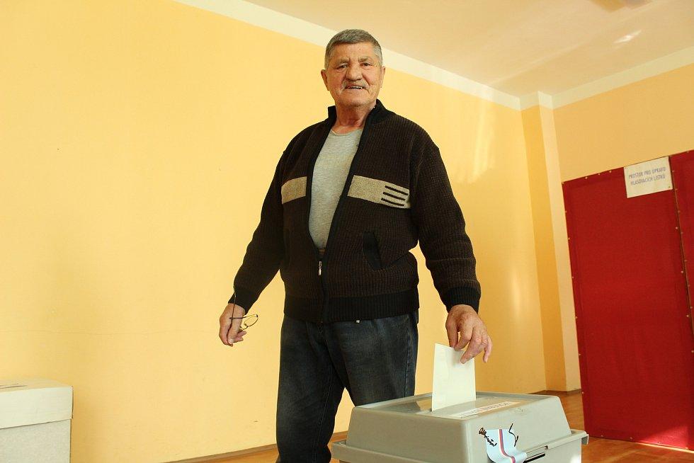 Volební místnost na Základní škole v Cihelní ulici v Bruntále. První volič z volebního okrsku hází svůj hlas do urny.