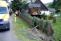 Při projetí pravotočivé zatáčky vyjel řidič mimo komunikaci, kde bokem skříňové nástavby vozu poškodil dům.