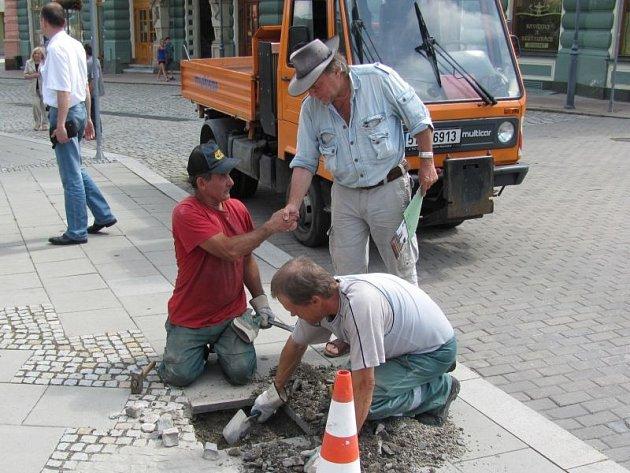 Německý umělec Gunter Demnig si před instalací stolpersteinů podal ruku s dlaždiči z technických služeb, kteří mu pomáhali. Dnes už je po Evropě na čtyřicet tisíc těchto kamenů.