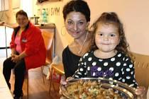 Karolínka Siváková v náručí Aurélie Balážové nad tácem plným lahodných bramborových placek. Romské pokrmy a speciality mohli ochutnat návštěvníci Veletrhu zdraví a sociálních služeb ve Společenském domě v Bruntále.