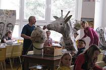 Děti ve výtvarné dílně Jaroslava Hrubého ve Městě Albrechticích vytváří z papíru obří žirafu. Ta bude  patřit mezi největší papírové sochy v České republice.