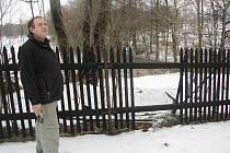 Vladan Žilinský ukazuje díru v plotě, kterou udělal zloděj, aby mohl odnést stromy.