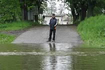 Silnice z Úvalna do polských Branic je stále zaplavená vodou, přestože včera téměř celý den nepršelo a hladina řeky Opavy klesala. Voda však tentokrát dala našemu okresu pokoj.