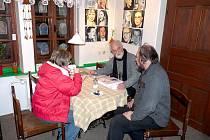 Fotograf Jindřich Štreit (vzadu) se spolumajitelem pensionu v Karlovicích Liborem Pavézkou (vpravo). Za nimi galerie osobností od výtvarnice Ivety  Dučákové.
