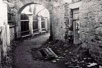 Farní ulička v Bruntále v době, kdy ji ve směru k zámku lemoval dřevěný plot. Vpravo je již neexistující vstupní branka na faru.