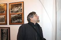 Fotograf Vlastimil Brabenec na výstavě fotografií ve velké síni bruntálského zámku. Na této výstavě, která právě probíhá, jsou k vidění snímky bruntálských autorů, svá díla tu má i Brabenec.