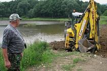 Bohumil Ramach z Českého rybářského svazu řídí budování improvizovaného nouzového přepadu, který na vodou naplněném rybníku Rusák stejně jednou měl v rámci rekonstrukce vzniknout.