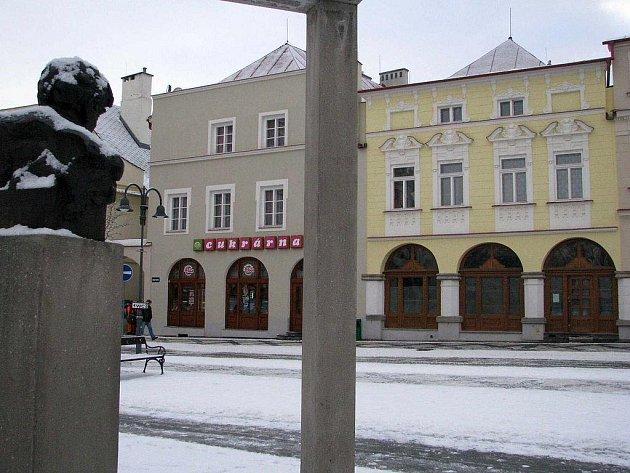 Busta Leopolda Bauera (vlevo) se ze svého památníku dívá na historický dům, ve kterém bude v Krnově do týdne otevřena Bauerova kavárna.