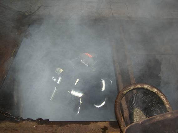 Práce hasičů při vyskladňování uhlí ze sklepa není jednoduchou záležitostí.