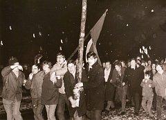"""Oslavy hokejové """"porážky Rusáků"""" na krnovském náměstí z okna komitétu opatrně sleduje sovětský důstojník."""