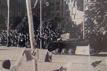 Tančík před krnovskou poliklinikou z 6. října 1938 místní vítali vlaječkami s hákovým křížem, vztyčenou pravicí nebo si ho jen zvědavě prohlíželi z chodníků.