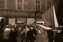 """Krnované slaví hokejovou """"porážku Rusáků"""" na krnovském náměstí. Nad jejich hlavami z okna sovětského komitétu opatrně vykukuje postava ve vojenské uniformě."""