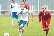 Fotbalisté Krnova měli blízko ke třem bodům, nakonec se museli spokojit s remízou. Na snímku uniká soupeři Jan Vavrečka (uprostřed v bílém), který ve druhém poločase nastřelil břevno. Vzadu přihlíží Miroslav Daříček.