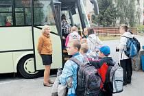Vychovatelky ze školní družiny na zastávce dohlížejí na to, aby děti nastoupily do správného autobusu.