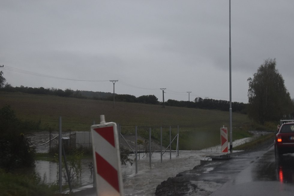 """V úseku u Krnova, kde se silnice první třídy změnila ve staveniště obchvatu, musí auta přes """"brod"""" . Naštěstí je brouzdaliště na silnici zatím mělké."""