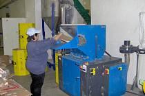 Antonie Blahutová obsluhuje drtič papíru ve výrobní hale v areálu dílen Střední školy PRAKTIK v Horním Benešově – Luhách.