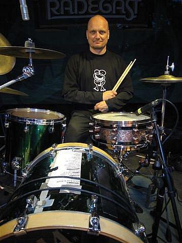 Bubeník Pavel Koudyš Koudelka ve svém novém tričku zepředu a zezadu. Bruntálský rodák si tričko se zubatou žábou hrdě oblékl na ostravský koncert skupiny Mňága a Žďorp.