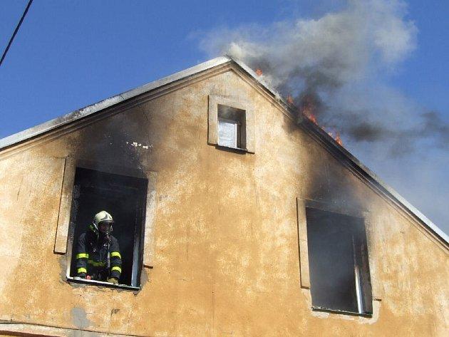 Zásah hasičům komplikovaly hustý kouř a vysoko šlehající plameny.