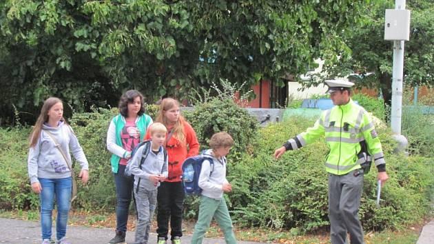 """Dopravní policisté pomáhají tento týden dětem u přechodů v blízkosti škol. Celorepubliková dopravně preventivní akce má název """"Zebra se za Tebe nerozhlédne""""."""