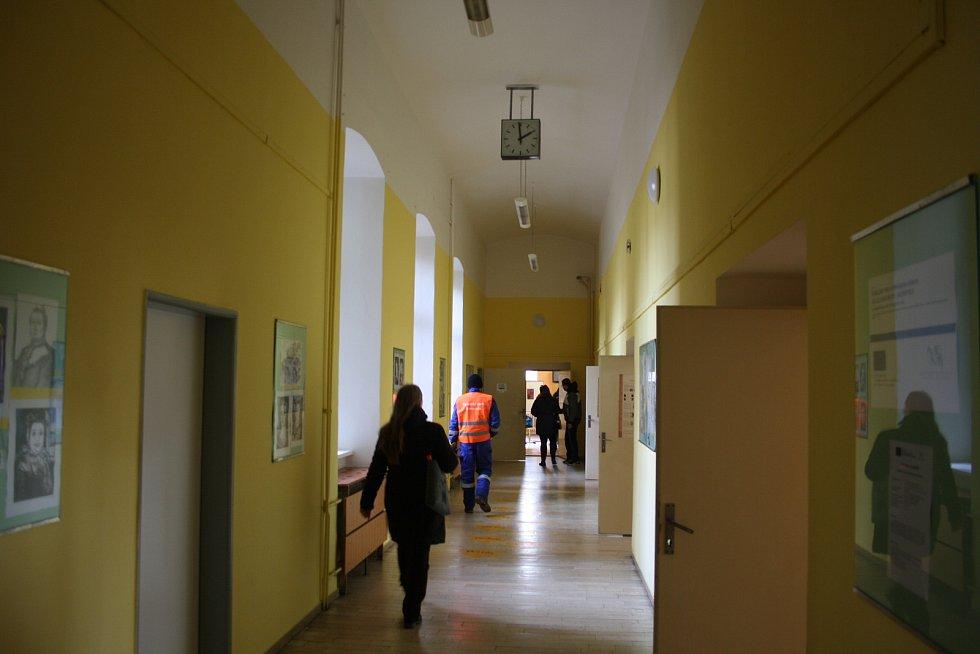 Volební místnosti na krnovském gymnáziu se buď otevřely o minutu dříve, nebo se hodiny na chodbě o minutu zpožďují.