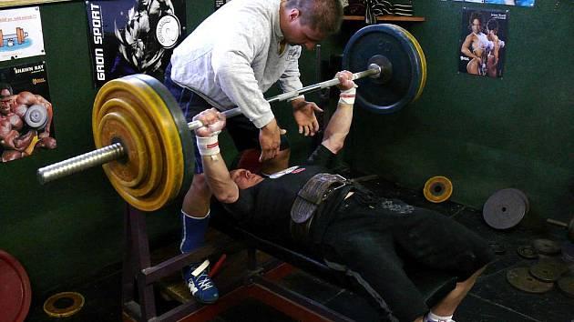 Václav Stuchlík (s činkou), oceněný za celoživotní přínos pro rozvoj mládežnického sportu, stále aktivně sportuje. Snímek z tréninku benchpressu.