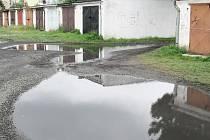 Garáže na Karáskově ulici se po každém dešti zaplní kalužemi, protože zde chybí kanalizace.