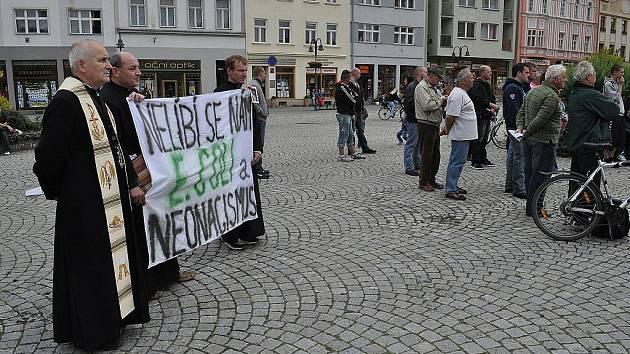 """Na krnovský míting Dělnické strany sociální spravedlnosti přišla fanoušků Tomáše Vandase také aktivistická skupina katolických kněžích, která rozvinila transparent """"Křesťané proti neonacismu"""" a """"Nemáme rádi E. Coli a neonacismus""""."""