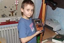 Jonáš Kučera si libuje nad knihou své oblíbené autorky Sandry Vebrové s názvem Luko, malý vlkodlak.
