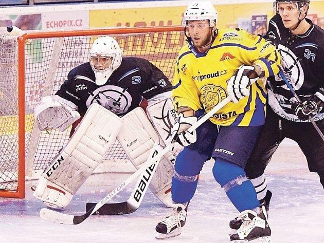 Krnovský hokejista Michal Tošenovjan (ve žlutém) se snaží stínit před brankou Českého Těšína.