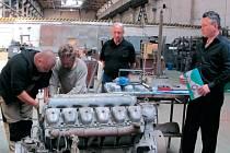 Zaměstnanci krnovské firmy Lakovna Zega si zvyšují kvalifikaci v rámci profesního vzdělávání. Jak si poradí s motorem lokomotivy, sledují odborný lektor Zdenek Telička a ředitel spolku Metal profesní vzdělávání Ostrava Michal Perout.